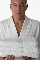 Portrait of a senior man holding a stack of folded towels