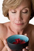 Close_up of a mature woman holding a bowl of water with floating flowers