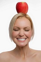 Close_up of a young woman balancing an apple on her head and smiling