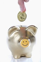 Close_up of a person´s hand putting a coin into a piggy bank