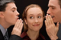 Two businessmen whispering to a businesswoman