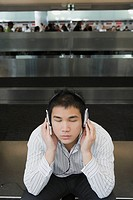 Businessman wearing headphones and listening to music at an airport