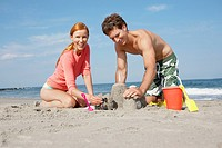 Young couple making sandcastle
