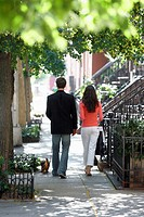 Young couple walking with dog on sidewalk rear view, Manhattan, New York City, New York, USA
