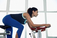 Young woman indoor cycling low angle view