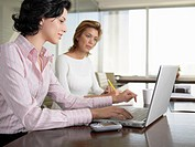 Two businesswomen using laptop computer
