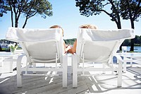 Couple holding hands and lying on lounge chairs