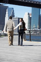 Couple walking on footbridge, woman looking back rear view, New York City, New York, USA