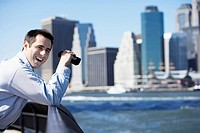 Man using binoculars and laughing, Manhattan in background, New York City, New York, USA
