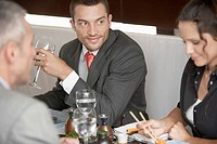 Businessman looking at woman eating sushi