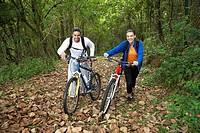 Couple with mountain bikes in forest