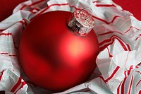 Red bauble on wrapping paper