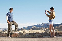 Woman photographing man by stone wall in desert, Death Valley, California, USA
