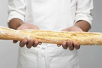 Chef holding baguette mid section