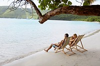 Mid adult couple on lounge chairs on beach high angle view, St. John, US Virgin Islands, USA