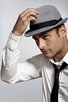 Mid adult man adjusting fedora