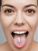 Vitamin pill on young woman´s tongue