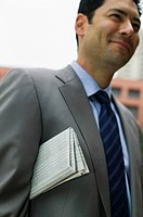 Mixed race businessman with newspaper