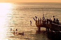 Silhouettes of people bathing from bathing platform in Ängelholm, Skåne, Sweden