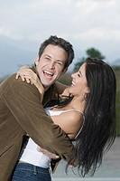 Laughing Hispanic couple hugging