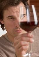 Closeup of man scrutinizing red wine