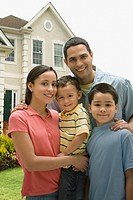 Hispanic family posing in front yard of home