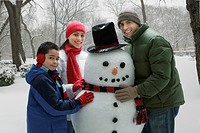 Hispanic family making snowman