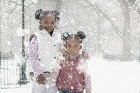 African sisters standing outdoors in falling snow