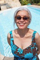 Woman at poolside in bathing suit and sunglasses