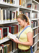 Young woman reading book in library (thumbnail)