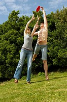 Two women jumping to catch a frisbee (thumbnail)