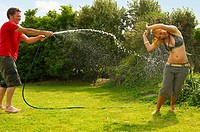 Man spraying woman with garden hose