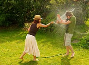 Woman spraying man with garden hose