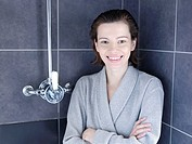 Woman in bathrobe standing in shower