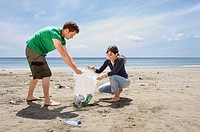 Young couple collecting garbage on beach