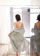 Woman heading to shower in bathrobe (thumbnail)