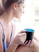 Woman looking out of window with mug