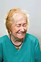 Head and shoulders portrait of an atttractive female blond haired senior citizen laughing
