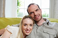 Couple sitting on couch, smiling