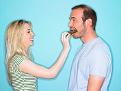 Young woman feeding man with cake