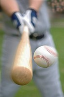Closeup of baseball player hitting ball