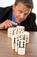Businessman Playing With Dominos