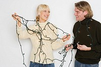 Couple untangling holiday lights