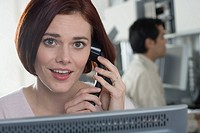 Woman talking on phone in office