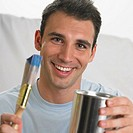 Man smiling and holding paintbrush and paint can