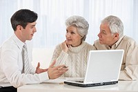 Businessman talking to senior couple in home