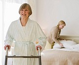 Senior woman using walker in bedroom