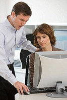 Businesswoman and businessman looking at computer