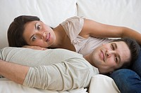 Multi_ethnic couple laying on sofa