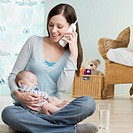 Mother on telephone with sleeping baby in her lap